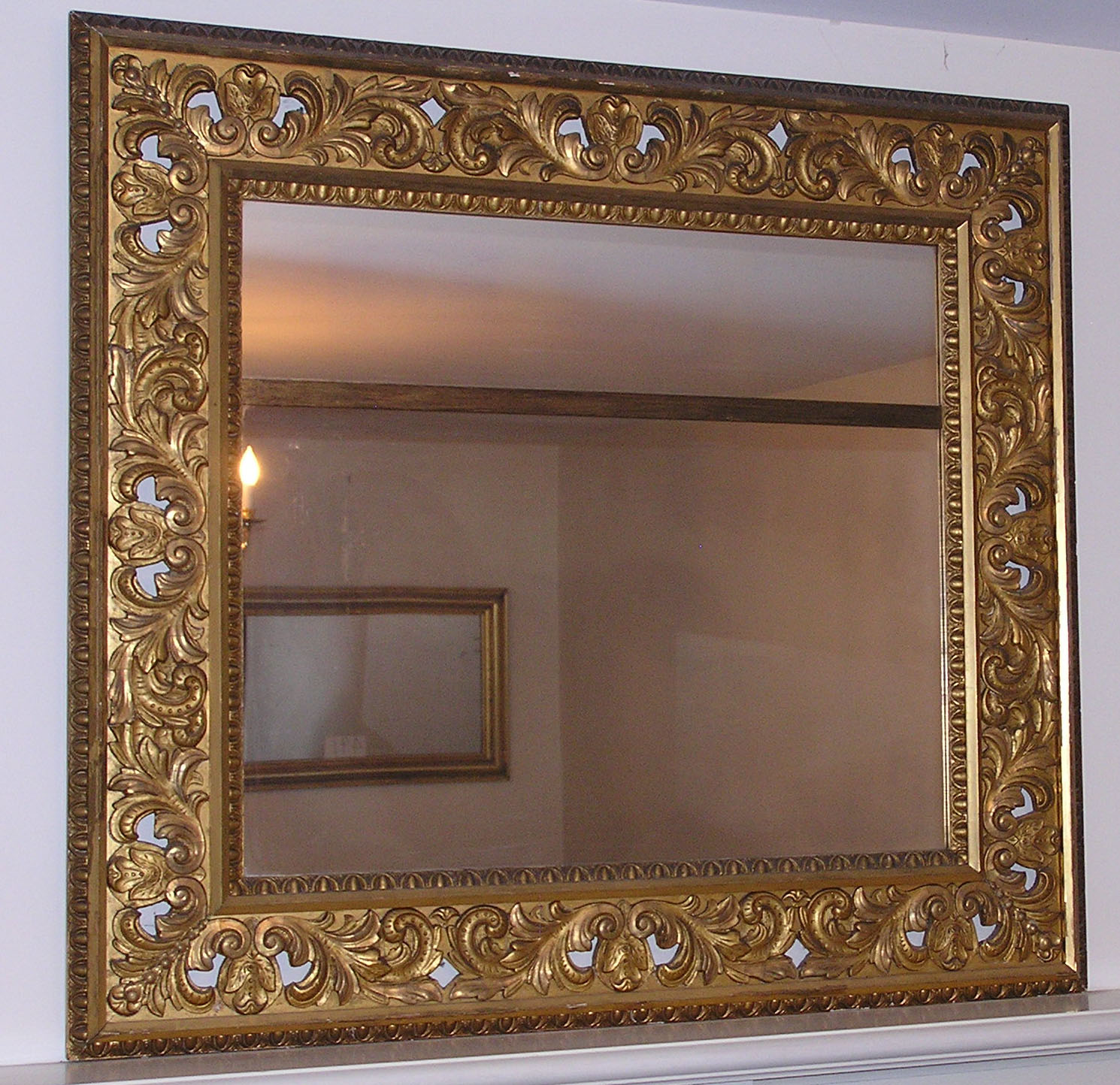An elaborately carved and pierced rococo revival gilt for Antique mirror