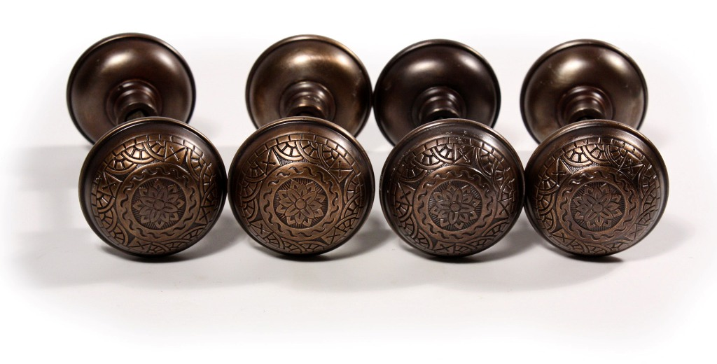 These are four matching antique door hardware sets by Russell & Erwin, with  bronze doorknobs and iron door plates with their original bronze wash. - Four Matching Antique Door Hardware Sets, Russell & Erwin, 1889