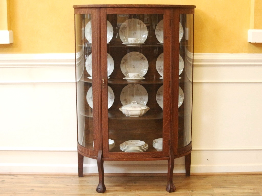 Antique oak bow front china cabinet with carved claw feet and a single bow glass door to the front. Inside there are 3 shelves with a plate grove and the ...