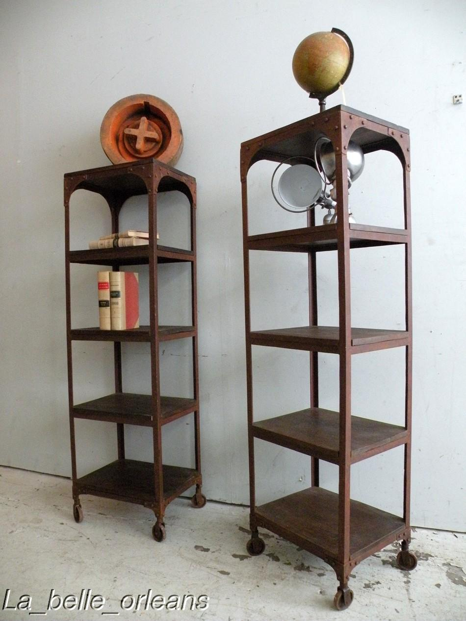 A charming pair of vintage industrial shelving etagere pieces , metal frame  with solid wood shelves on cast metal wheels. A fantastic rusty  patina/color.